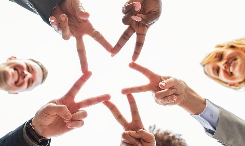 Eine Gruppe aus fünf Menschen formt mit ihren Fingern gemeinsam einen Stern, fotografiert von unten