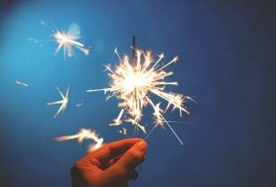 Bild einer Hand, die eine brennende Wunderkerze hält, blauer Hintergrund