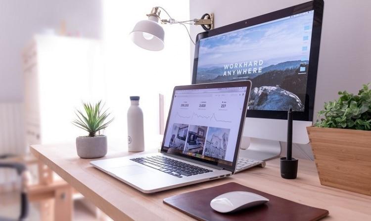 Ansicht eines Schreibtisches mit Laptop und Bildschirm, der die Ergebnisse einer Internetrecherche zeigt