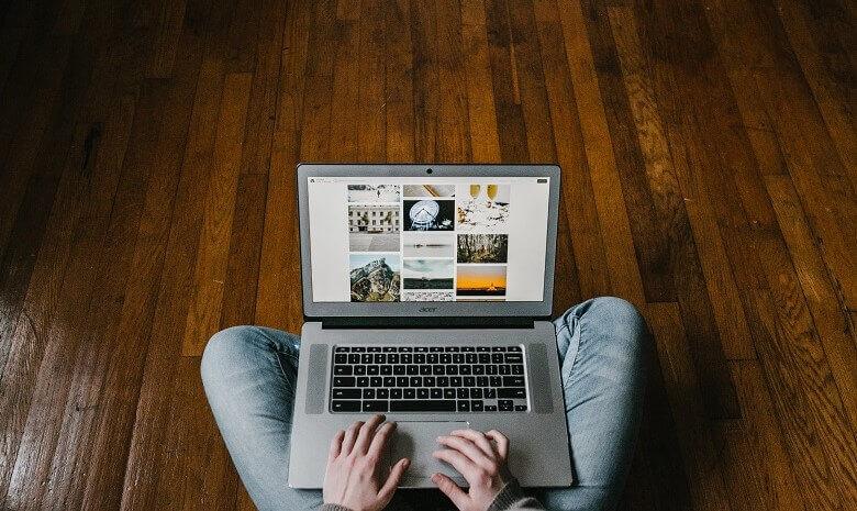 Laptop auf dem Schoß einer Person, auf dem Bildschirm ist eine Reihe von Bildern für die Recherche zu sehen