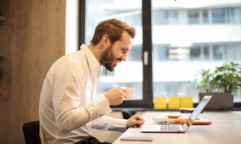 Artikelbild Storytelling 2: Ein lachender Mann sitzt mit einer Kaffeetasse in der Hand vor seinem Laptop.