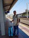 Der Autor des Monats steht mit seinem Koffer am Bahnsteig und lacht in die Kamera.