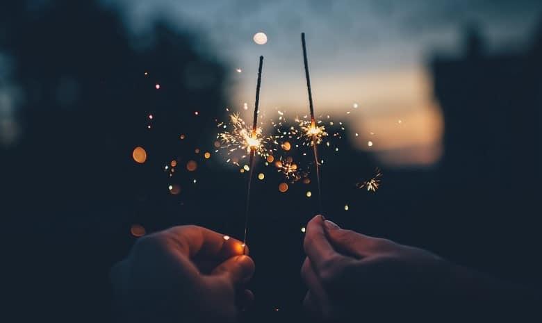 Bild zum Autor des Monats Jubiläum; zwei Hände halten brennende Wunderkerzen vor einem dunklen Hintergrund