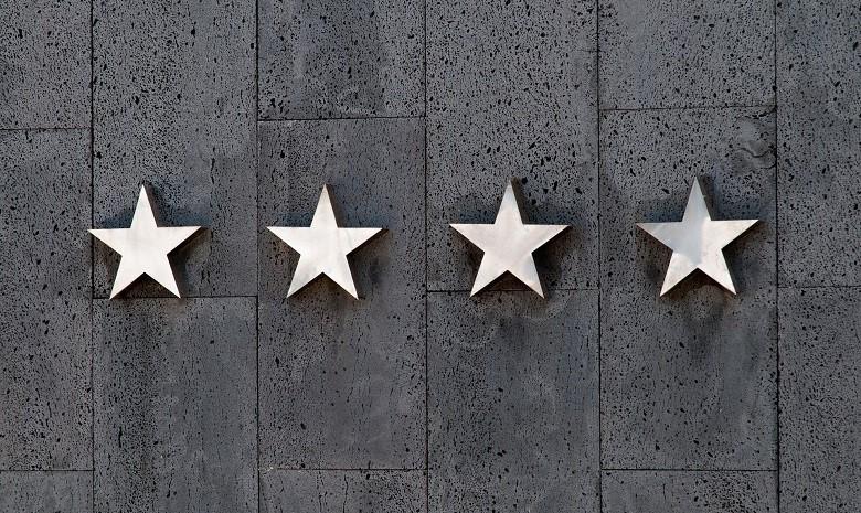 Textbroker Autorengremium 2019 Beitragsbild 2: Vier Sternsymbole an einer grauen Mauer