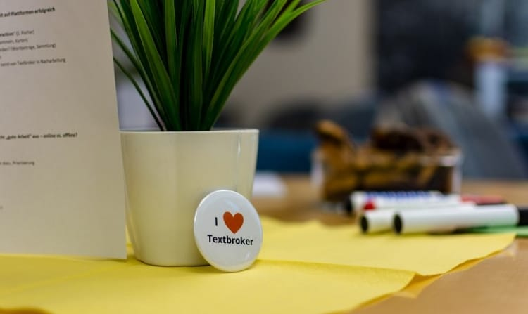 """Textbroker Autorengremium 2019 Headerbild: Ein Anstecker mit """"I"""