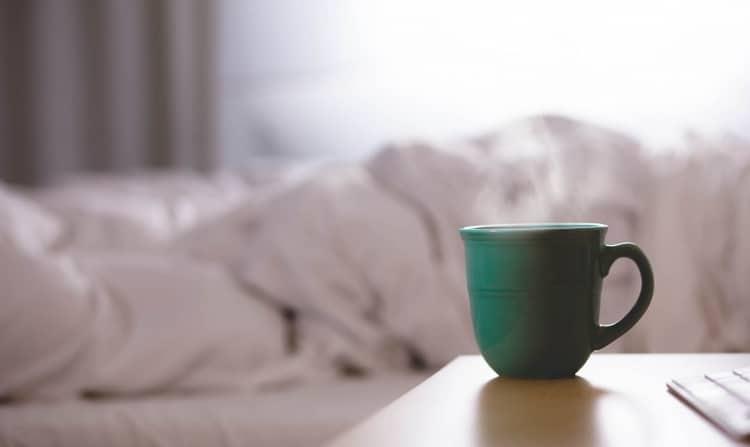 Krankengeld für Freelancer Headerbild: Eine dampfende Tasse Tee steht im Vordergrund, im Hintergrund ist ein zerwühltes Bett zu sehen.