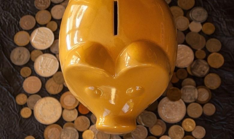 Krankengeld für Selbstständige Beitragsbild 3: ein gelbes Sparschwein sitzt auf einem Haufen Münzen