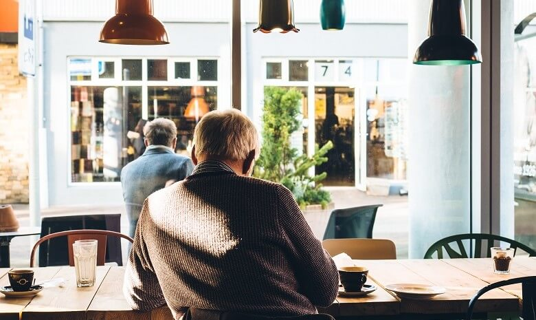 Krankengeld für Selbstständige Beitragsbild: Ein Rentner sitzt mit einer Tasse Kaffee in einem Café