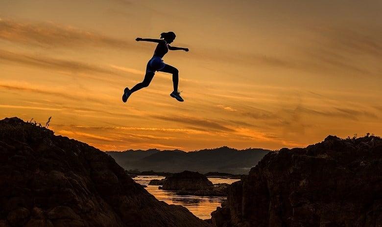 Tipps für Texter 2020 Beitragsbild 1: Eine Sportlerin springt über vor einem Sonnenuntergang einen Abgrund hinüber.