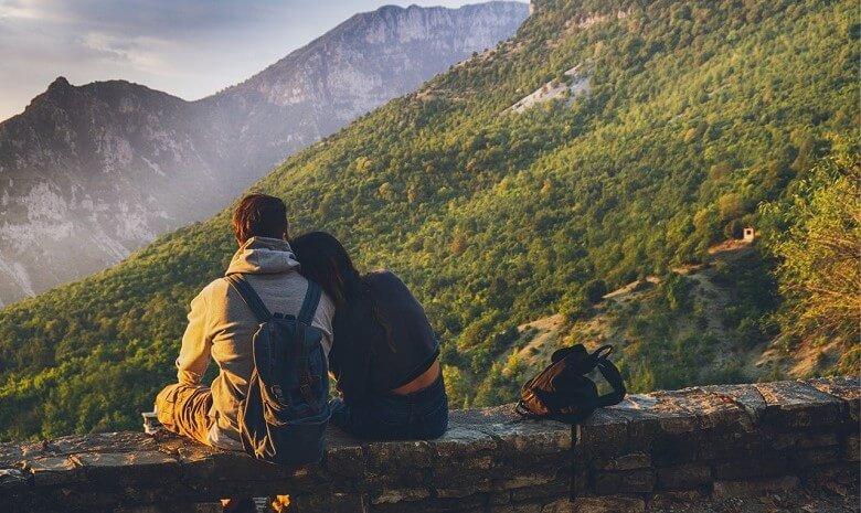 Tipps für Texter 2020 Beitragsbild 4: ein Paar in Wanderausrüstung sitzt auf einer Mauer mit Ausblick auf die Berge.