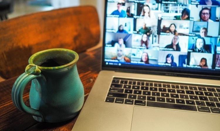 Autorengremium Start Texter Header: Ansicht eines Laptops mit einer Videokonferenz auf dem Bildschirm, im Vordergrund eine türkisgrüne Tasse