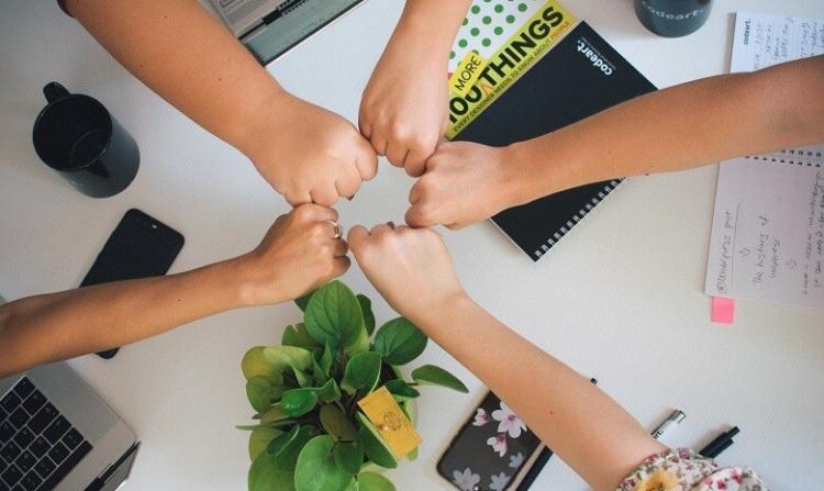 Leichte Sprache schreiben Headerbild: Fünf Menschen halten die Fäuste in einem Gruppen-Fist-bump über einem Tisch mit Schreibutensilien zusammen