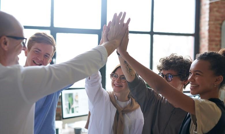 Firmenporträt schreiben Beitragsbild 2: Fünf Menschen geben sich gegenseitig ein High Five und lachen sich an.