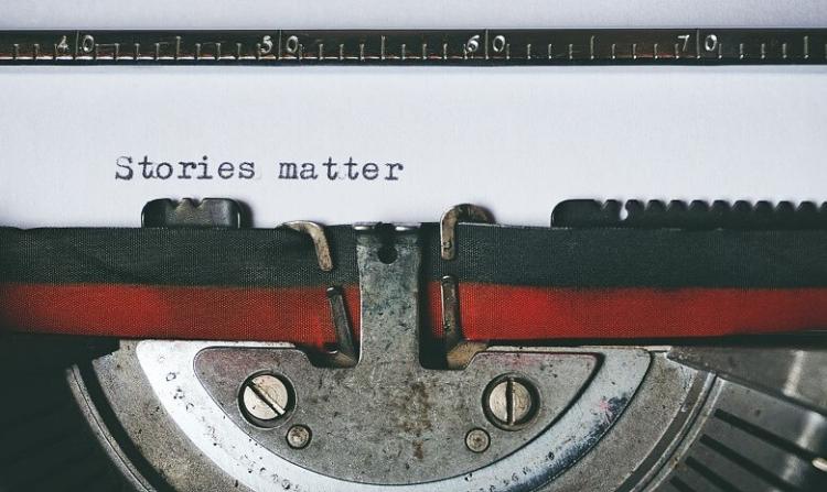 """Firmenporträt schreiben Headerbild: Nahaufnahme eines Blatts in einer Schreibmaschine mit der Aufschrift """"Stories matter"""""""