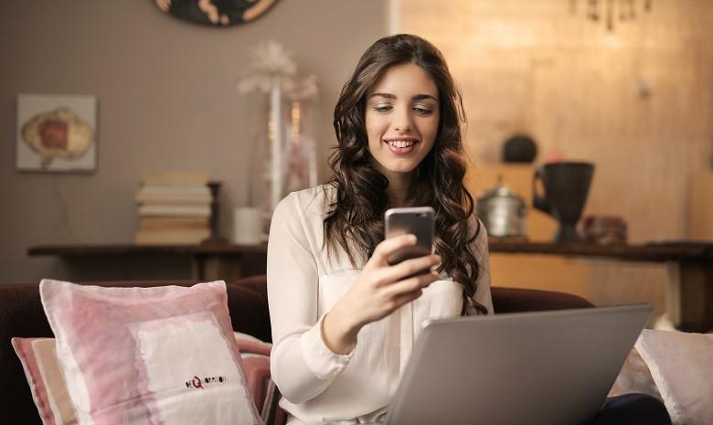 Call-to-Action schreiben Beitragsbild 1: Eine junge Frau sitzt auf ihrem Sofa, den Laptop auf dem Schoß, und schaut auf den Bildschirm ihres Smartphones, das sie in der rechten Hand hält.