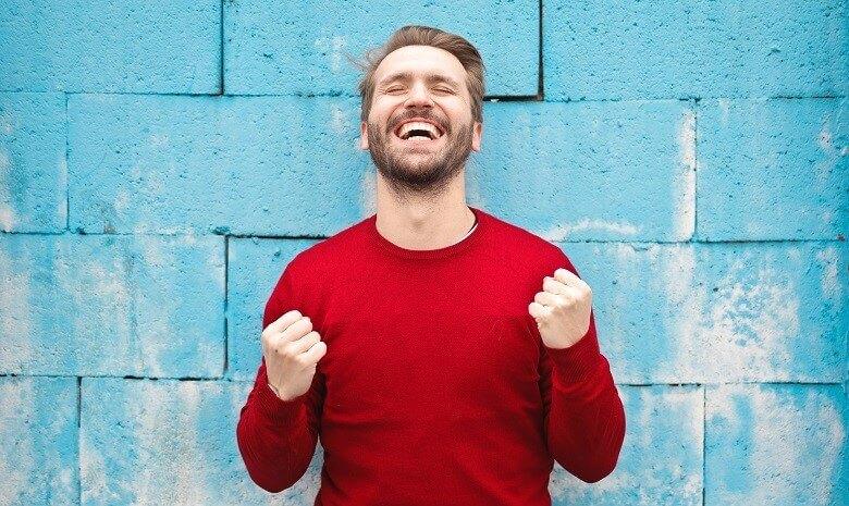 Call-to-Action schreiben Beitragsbild 2: Ein Mann steht vor einer blauen Wand, die Fäuste in einer triumphierenden Geste nach oben gestreckt.