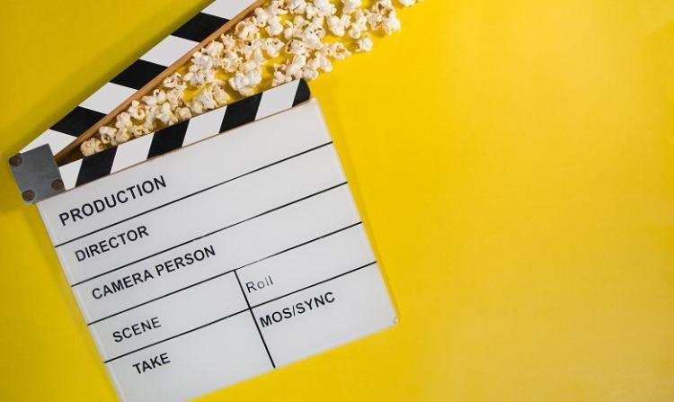 Call-to-Action schreiben Headerbild: Ein Klappboard aus der Filmproduktion liegt auf einem gelben Hintergrund, umgeben von Popcorn.