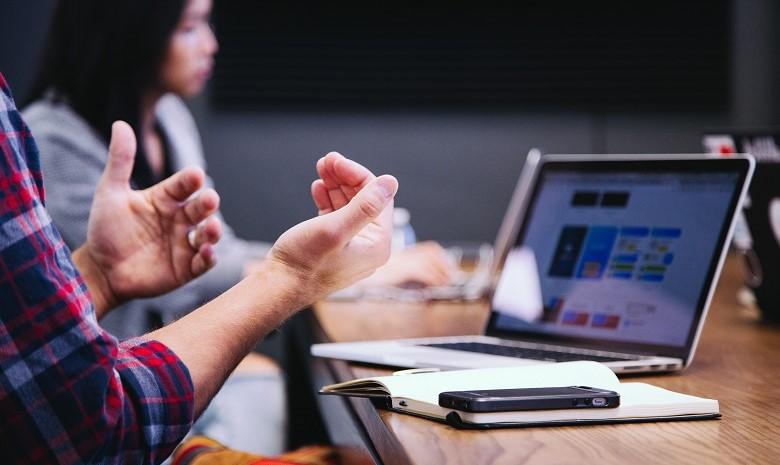 Ein Mann gestikuliert im Gespräch mit seinen Händen. Vor ihm steht sein Laptop.