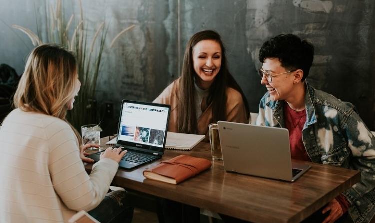 Eine Gruppe junger Menschen sitzt um einen Tisch und unterhält sich fröhlich.