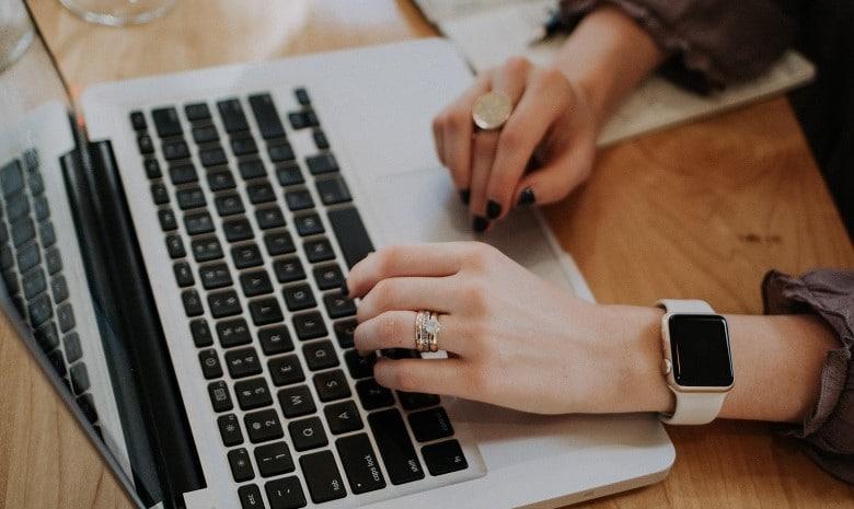 Nahaufnahme der Hände einer Frau, die Tastatur und Mauspad ihres Laptops nutzt.
