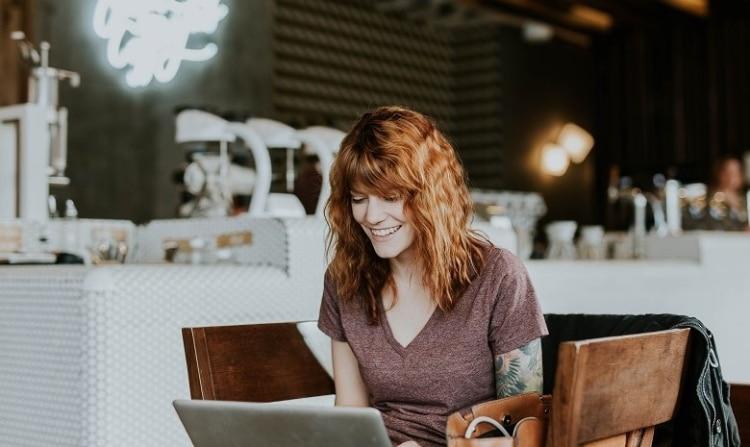 Eine junge Frau sitzt im Café und lacht über etwas, das sie auf ihrem Laptopbildschirm sieht.